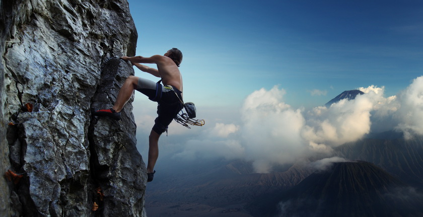 Young man climbing natural rocky wall with volcanoes on the back