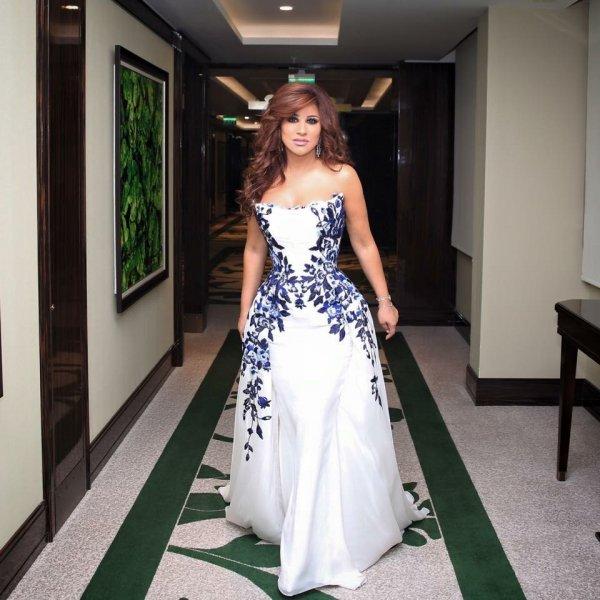 كرم ترتدي فستان بالتنورة الكبيرة الواسعة والمزين بورود زرقا