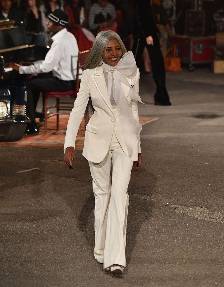 تومي هيلفيغر وإحدى تصميماته للبدل النسائية البيضاء
