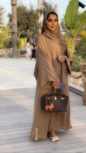 تصميم مميز لعباءة من اللون البيج ترتديها مدونة الموضة فاطمة المازمي